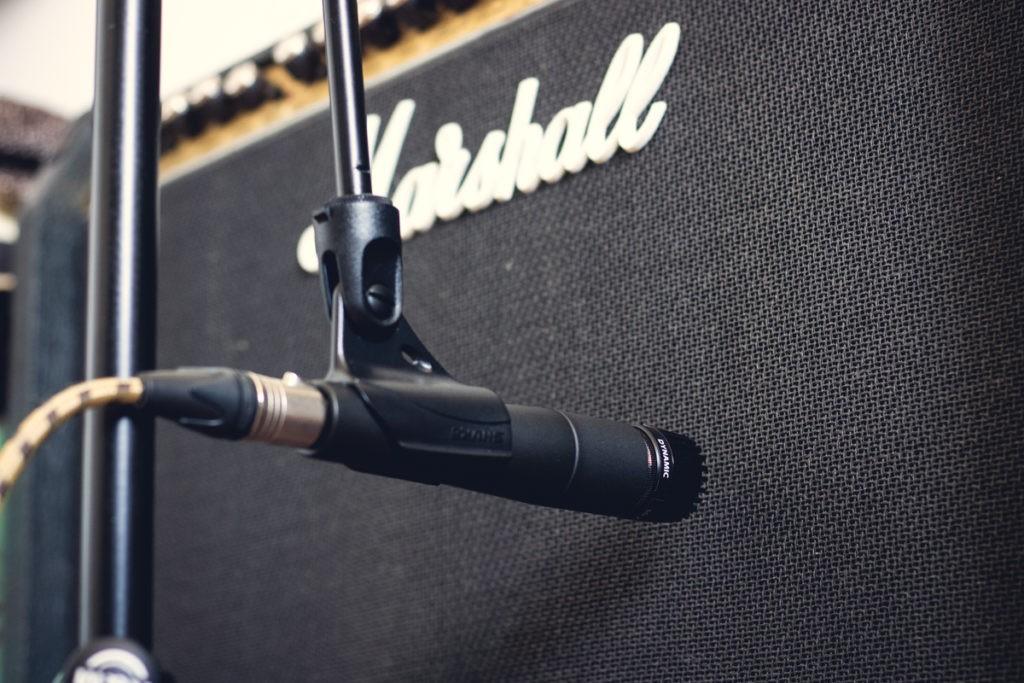 Un microphone enregistrant un ampli de guitare électrique